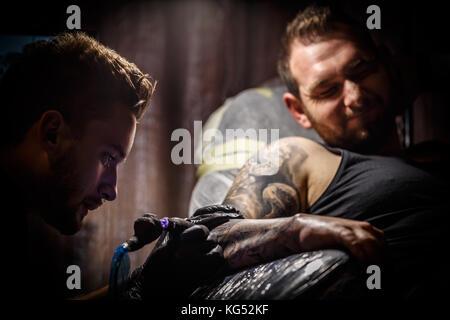 Professionelle Tätowierer macht ein Tattoo auf die Hand eines jungen Mannes - Stockfoto