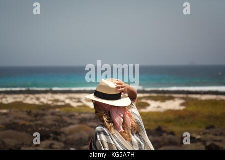 Mädchen mit Hut und Blick auf das Meer stehen auf dem Felsen. Lanzarote Canarias - Stockfoto