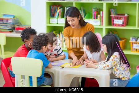 Asiatische Frau Lehrer Lehre gemischten Rennen Kinder Lesung buchen Sie im Klassenzimmer, Kindergarten Vorschule Konzept