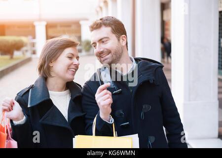 Mann hält eine Kreditkarte für die Einkaufen, Zeit mit seiner Freundin bereit - Stockfoto
