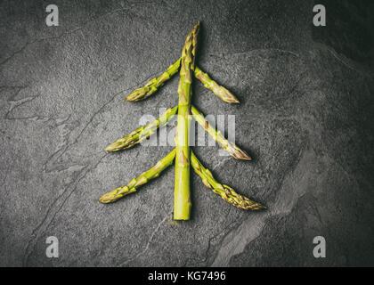 Weihnachten Lebensmittel Hintergrund. Weihnachtsbaum aus frischen Spargel auf schwarzen Stein Schiefer Hintergrund. - Stockfoto