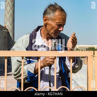 Man Schweißnähte Tor nur mit seiner Hand als Eye Shield in Samarkand, Usbekistan, 19. Mai 2017 - Stockfoto