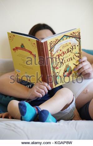 Schwangere Frau lesen junge polnische Buch mit verschiedenen Kind Geschichten beim zusammen sitzen auf einem Sofa - Stockfoto