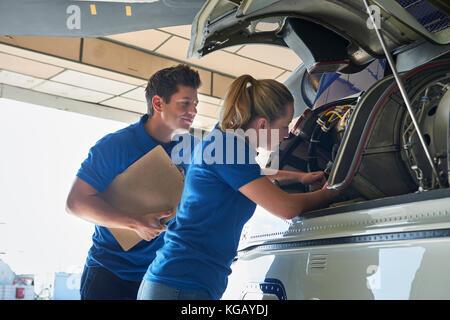 Aero Ingenieur und Lehrling Arbeiten am Helikopter im Hangar - Stockfoto