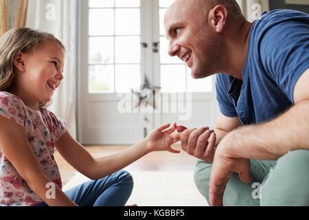 Vater und Tochter sitzen auf dem Boden sprechen zu Hause - Stockfoto