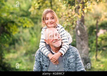 Großvater, seine Enkelin auf seine Schultern. - Stockfoto