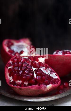 Ein Stück reifer Granatapfel auf einer hölzernen Hintergrund ausschneiden. Selektive konzentrieren. - Stockfoto