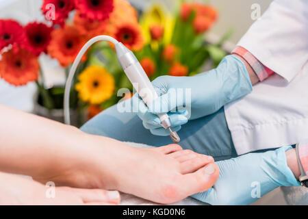 Nahaufnahme der Hand einer pedicurist das Tragen steriler OP-Handschuhe während der Verwendung eines Toe Nail Clipper, - Stockfoto