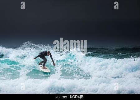Ein einsamer Surfer auf einer Welle als dunkle Wolken über der Küste von North Cornwall. - Stockfoto