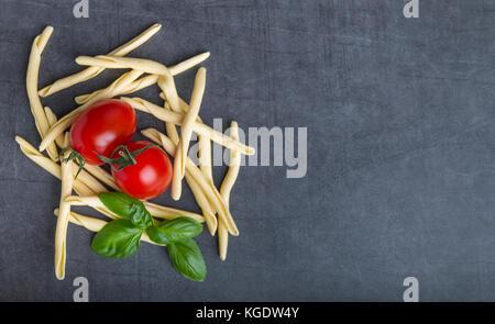 Raw italienische Pasta mit Tomaten eine Basilikum auf einem Steintisch, Ansicht von oben - Stockfoto