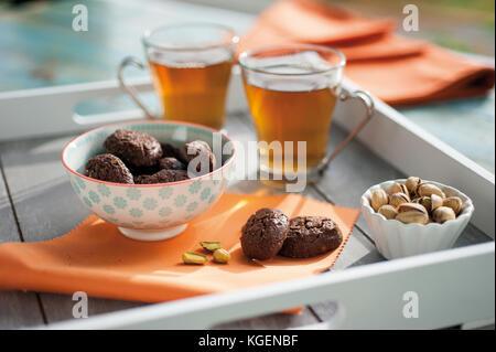 Rustikale Kekse mit Schokolade und Nüsse in Keramik Schale, auf Holz Tablett serviert mit zwei Tassen Tee und einer - Stockfoto