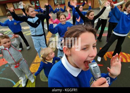Penyrheol Grundschule, Gorseinon, Swansea. Zoe Owens führt die Routine mit dem karaeoke Mikrofon für die Mittagszeit - Stockfoto