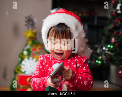 Baby Mädchen spielen Handy Tragen santa hut - Stockfoto