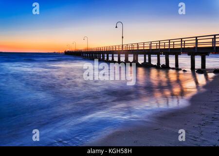 Historischen Fachwerkhäuser Steg zum Angeln und Erholung in Port Philip Bay vor Port Melbourne Sandstrand bei Sonnenuntergang. - Stockfoto