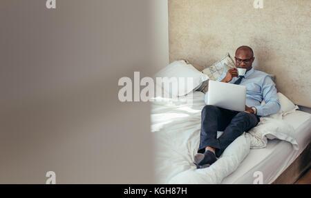 Mann in formelle Kleidung Arbeiten am Laptop im Bett lag. Unternehmer Arbeiten am Laptop beim Trinken von Kaffee - Stockfoto