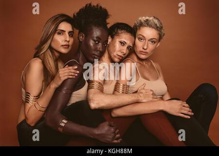 Gruppe von unterschiedlichen Frauen gemeinsam gegen braunen Hintergrund sitzen. Multi-ethnische Frauen mit unterschiedlichen - Stockfoto