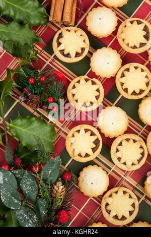Weihnachten Auswahl an Mini frosted Mince Pies und Stechpalme Blätter auf einen tartan Hintergrund - Stockfoto