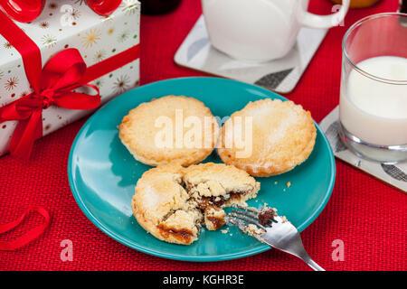 Hausgemachte frische Kuchen und ein Glas Milch für Weihnachten auf einem roten hessische Tischdecke mince - Stockfoto