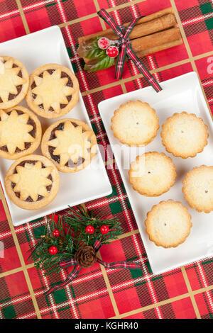 Zwei kleine weiße Platten mince pies für Weihnachten mit Zimtstangen auf einem tartan Hintergrund - Stockfoto