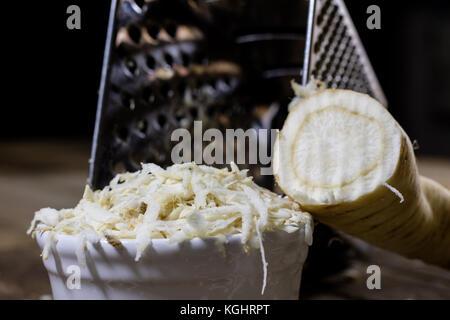 Wurzel Petersilie Wurzel auf Reibe. Rost und Petersilie auf der alten Küche Tisch in der Küche. schwarzer Hintergrund - Stockfoto
