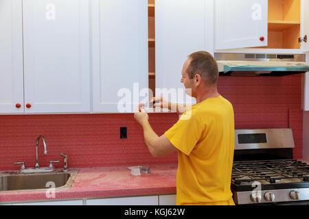Einbau Küche. Arbeitskraft wird auf Küchenschrank Türen installiert ...