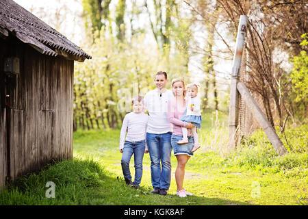 Gerne vier Mitgliedstaaten Familie Ausgaben Frühling Nachmittag gemeinsam im Freien im Orchard - Stockfoto