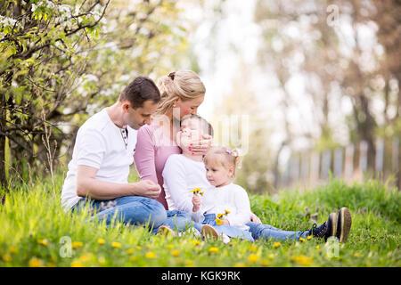 Gerne vier Mitgliedstaaten junge Familie Ausgaben Frühling Nachmittag gemeinsam im Freien im Obstgarten, sitzen - Stockfoto