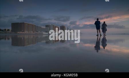 Junger Mann und eine Frau, die am Ufer am Strand gegen Himmel bei Sonnenuntergang, Daytona, Florida, USA - Stockfoto