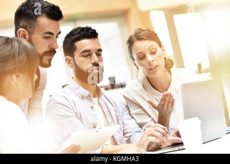 Design Team Meeting und Arbeiten am Laptop - Stockfoto