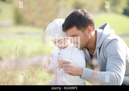 Daddy mit Baby Mädchen Blumen pflücken in Landschaft, Herbst Tag - Stockfoto