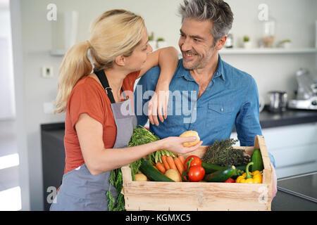 Portrait von Paar in der heimischen Küche holding Korb mit frischem Gemüse - Stockfoto