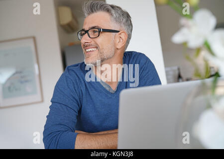 Mann im mittleren Alter, die von zu Hause aus arbeiten - Büro auf Laptop - Stockfoto