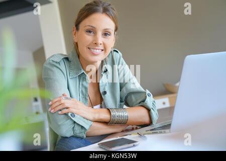 Trendige Mädchen von zu Hause aus arbeiten am Laptop - Stockfoto