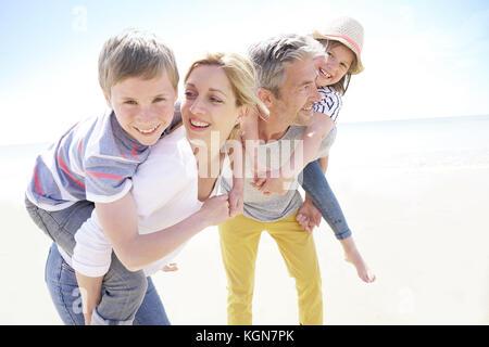 Eltern geben piggyback Ride für Kinder am Strand - Stockfoto