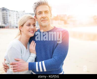 Im mittleren Alter Paar zusammen zu Fuß am Sandstrand - Stockfoto