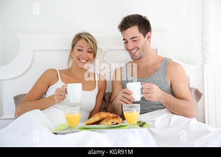 Fröhlicher junger Paar Frühstück im Bett - Stockfoto