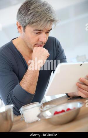 Mann an der Rezeptur auf Digital tablet Suche Kuchen vorbereiten - Stockfoto