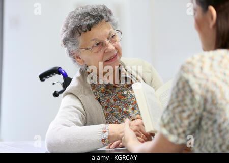 Arer homec lesen Buch alte Frau im Pflegeheim - Stockfoto