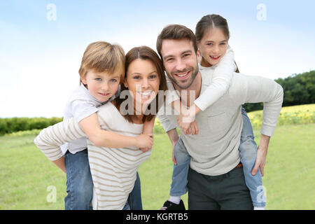 Junge Eltern geben piggyback Ride für Kinder - Stockfoto