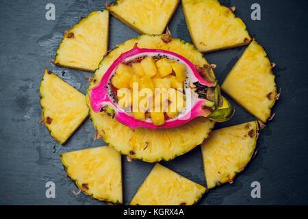 Auf einem schwarzen Hintergrund, frische Ananas, Drachenfrucht - Stockfoto