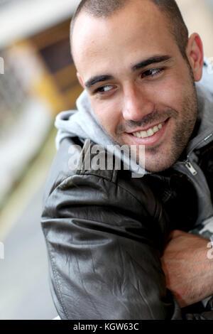 Lächelnden jungen Mann mit Leder Jacke in der Stadt - Stockfoto