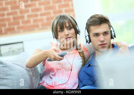 Junges Paar im Sofa Fernsehen mit Kopfhörern - Stockfoto
