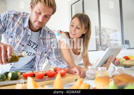 Freundliche Paar in der Küche kochen Abendessen, mit Tablet - Stockfoto