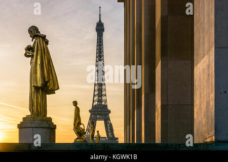 Die aufgehende Sonne beleuchtet die goldenen Statuen auf der Esplanade Trocadero und dem Eiffelturm sich gegen eine - Stockfoto