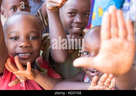 Ein Bündel von gelegentlichen ugandischen Kinder auf der Straße lachen, Lächeln, winken und Spaß vor der Kamera. - Stockfoto