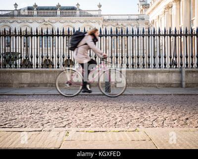 Eine Frau fährt mit dem Fahrrad oder mit dem Fahrrad entlang der King's Parade Cambridge vor Kings College der Universität Cambridge Stockfoto