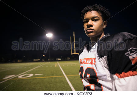 Portrait zuversichtlich, haltbare Teenager an der High School Football Player auf Fußballplatz bei Nacht - Stockfoto