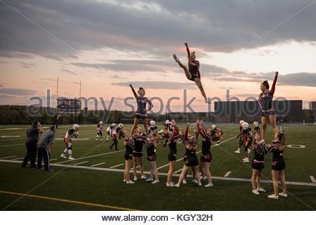 Junges Mädchen High School Cheerleading Team jubeln und springen auf Nebenerwerb von Spiel auf Fußball-Feld - Stockfoto