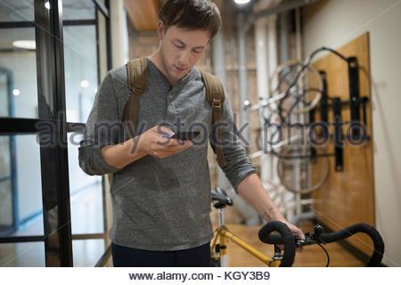 Kreative Geschäftsmann Wandern Fahrrad und texting mit Smart Phone im Büro Flur - Stockfoto