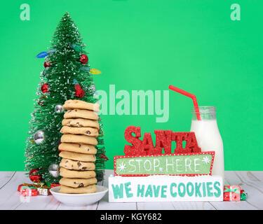 Chocolate Chip Cookies 12 Hoch auf eine kleine runde Platte gestapelt, Weihnachtsbaum Glas Flasche Milch mit Stroh - Stockfoto